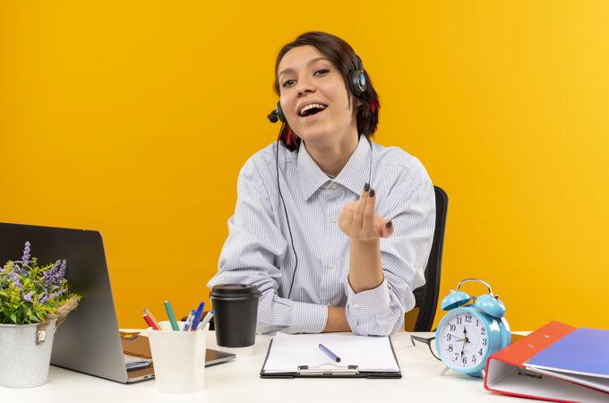 快乐的年轻呼叫中心女孩戴着耳机坐在办公桌旁做着来这里的手势孤立在橙色上