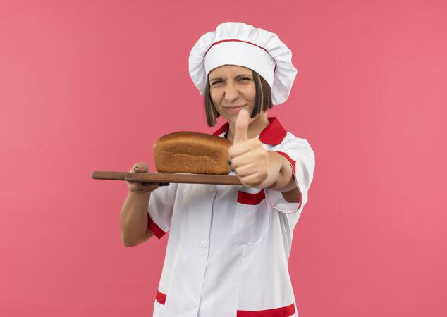 身着厨师制服的年轻女厨师手拿着插有面包的砧板 在粉色背景上孤立地竖起大拇指 并留有复印空间