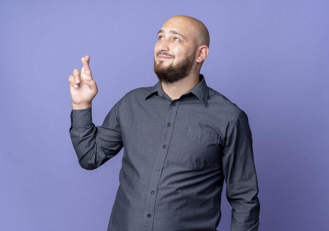 高兴的年轻秃头呼叫中心男子抬头做交叉手指手势孤立的紫色背景