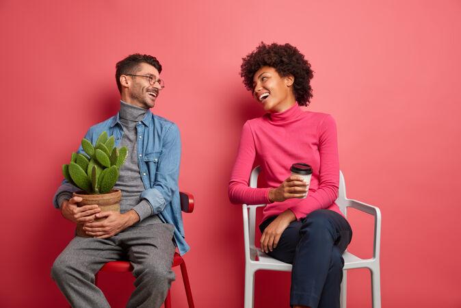 快乐的多民族的女人和男人有愉快的谈话互相看着并且在椅子上摆姿势