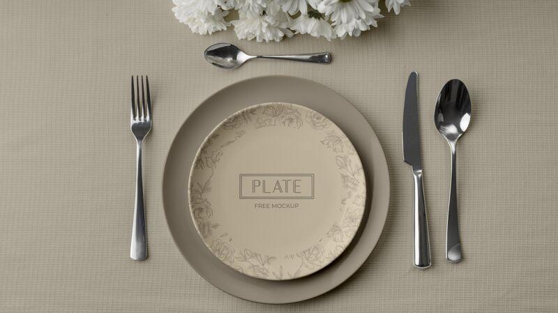 平铺的盘子放在桌子上 有餐具和鲜花