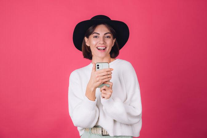 穿着白色休闲毛衣 戴着红粉色帽子的时髦女人