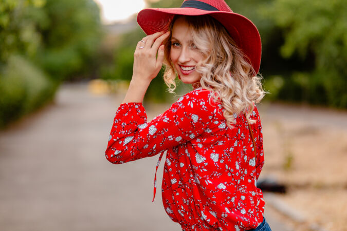 美丽迷人的时尚金发微笑的女人在稻草红帽子和衬衫夏季时尚服装