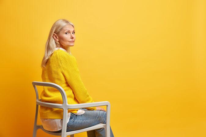 平静美丽的五十岁老太太独自坐在椅子上思考生活穿着黄色针织毛衣和牛仔裤空白复制空间