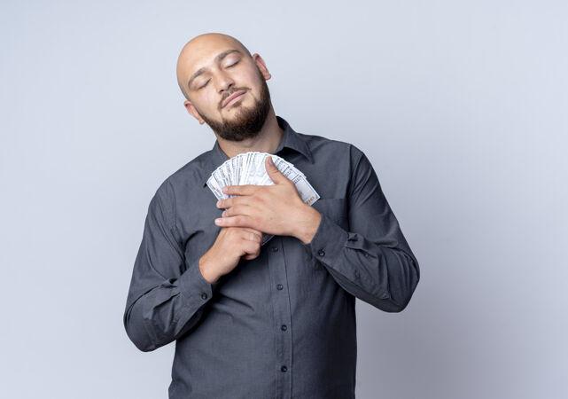 高兴的年轻秃头呼叫中心男子抱着钱闭着眼睛隔离在白色背景与复制空间