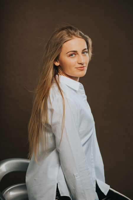 一个迷人的金发女性坐在吧台上摆姿势的垂直镜头