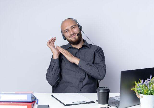 高兴的年轻秃头呼叫中心男子戴着耳机坐在办公桌旁与工作工具保持手靠近另一个孤立的白色背景