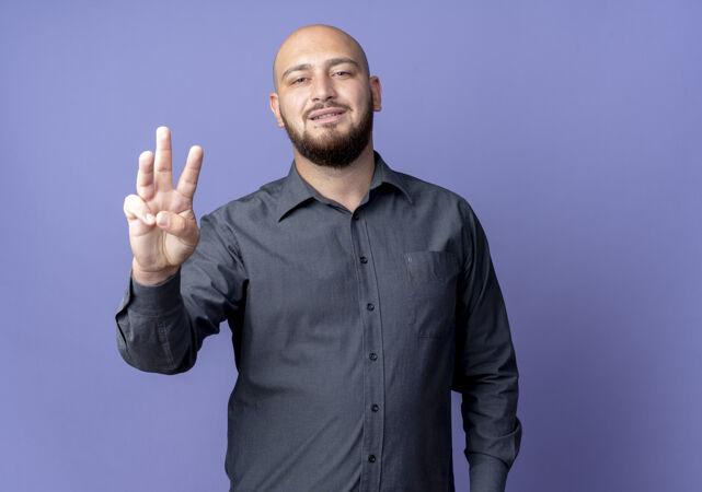高兴的年轻秃头呼叫中心男子显示三个与手隔离在紫色背景与复制空间