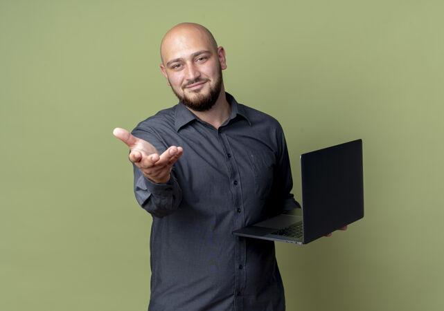 高兴的年轻秃顶呼叫中心男子手持笔记本电脑 伸出手对着相机隔离在橄榄绿的背景与复印空间