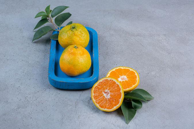 把一个橘子放在盘子里 旁边放着一片橘子叶 背景是大理石