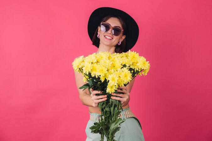 漂亮时尚的女人戴着帽子和墨镜摆姿势 捧着一大束黄紫苑 春意盎然 积极向上的情绪与世隔绝