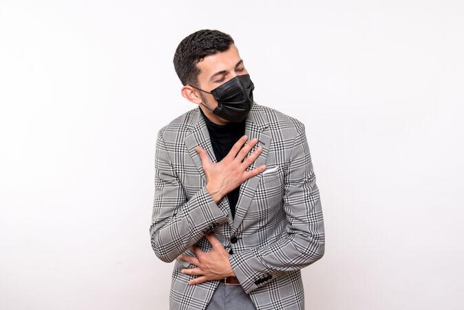 正面图:戴着黑色面具的年轻人把手放在胸前 站在白色的隔离背景上
