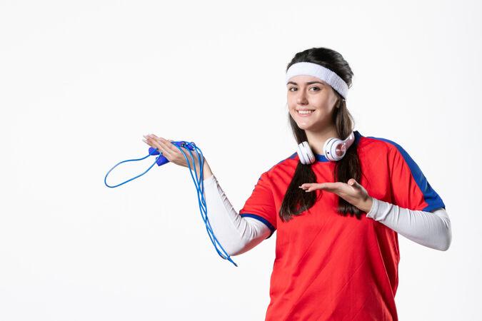 正面图白色墙壁上穿着运动服跳绳的年轻女性