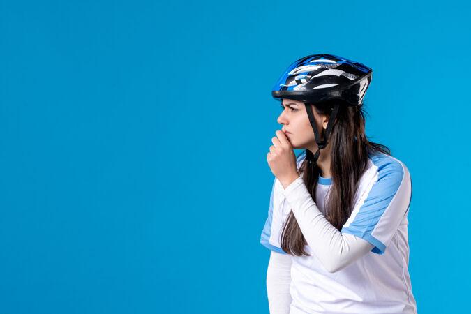 前视图穿着运动服的年轻女性 蓝色墙上戴着头盔