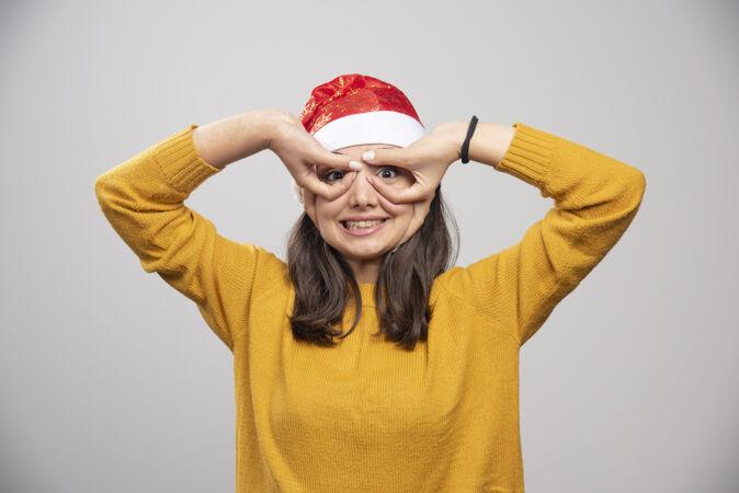 戴圣诞帽的女人在展示她的瞳孔