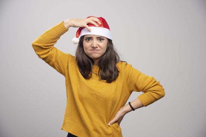 戴着圣诞老人红帽子的年轻女子在白墙上摆姿势