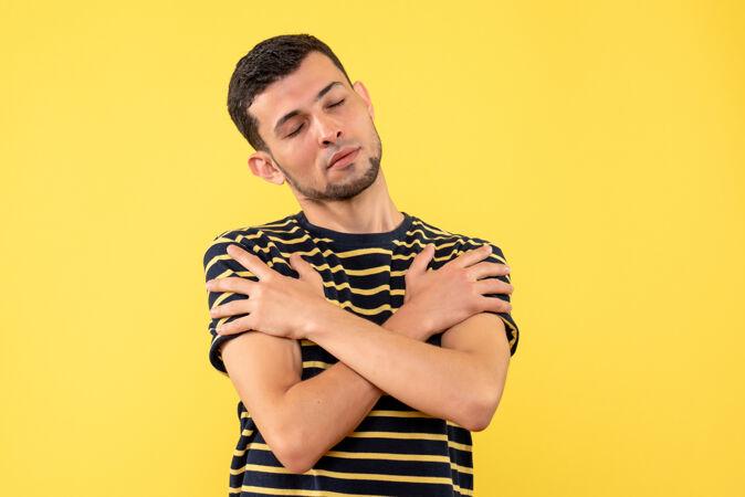 正面图:年轻人闭着眼睛双手交叉在黄色孤立的背景上