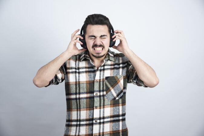 戴着耳机听白墙上的歌的帅哥的画像