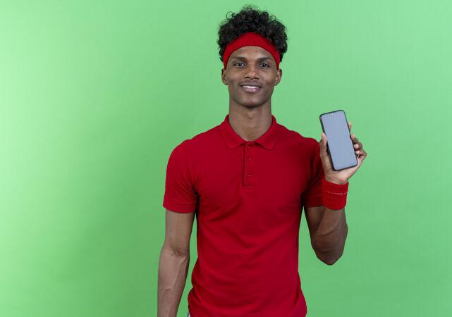 高兴的年轻黑人美国运动男子戴着头带和手环举行电话隔离在绿色的墙壁上