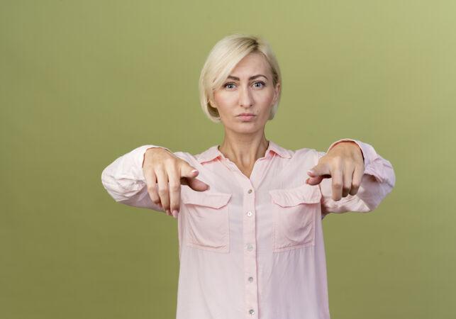 自信的年轻金发斯拉夫女人在橄榄绿的墙上向你展示孤立的姿态