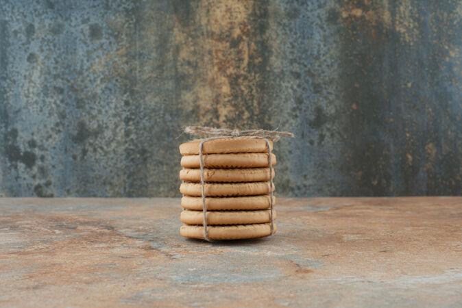 甜甜的圆形饼干在大理石背景绳
