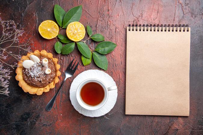 俯瞰一杯茶和美味的小蛋糕在一张深色的桌子上甜点饼干