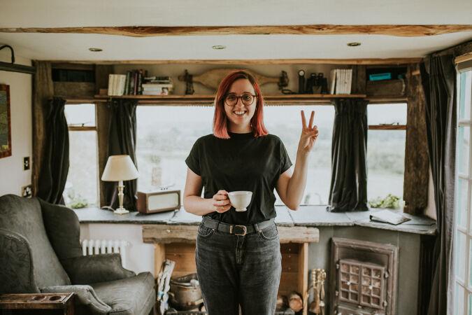小屋里拿着咖啡杯的女人