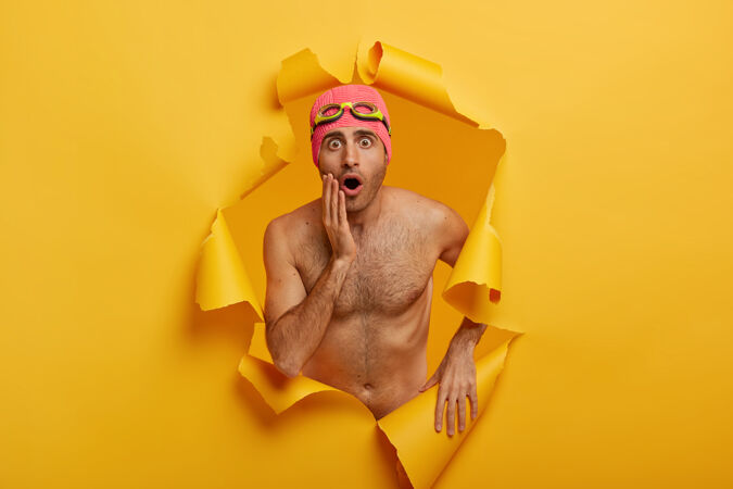 照片中的年轻人赤裸上身站着 身为专业游泳运动员 注意到一些不可思议的事情 戴着护目镜和泳衣