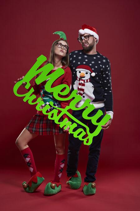 穿着圣诞服装的快乐的书呆子夫妇