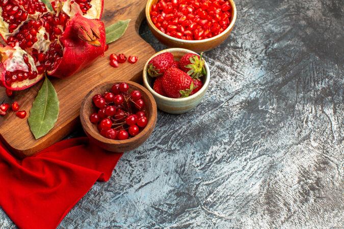前视图切片石榴新鲜的红色水果在一个浅黑色的桌子上