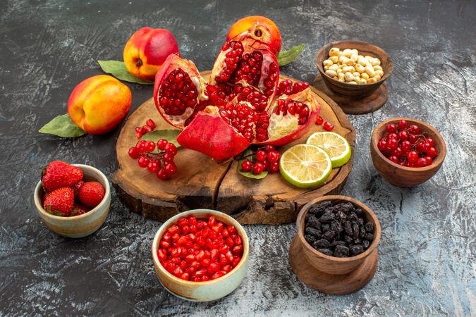 正面图浅黑色桌上的水果园树上的切片石榴和桃子