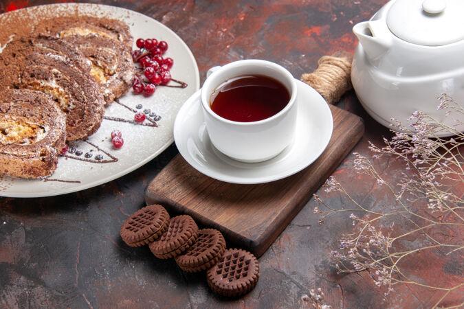 半俯视图美味饼干卷与饼干和茶在黑暗的桌子上甜饼饼蛋糕