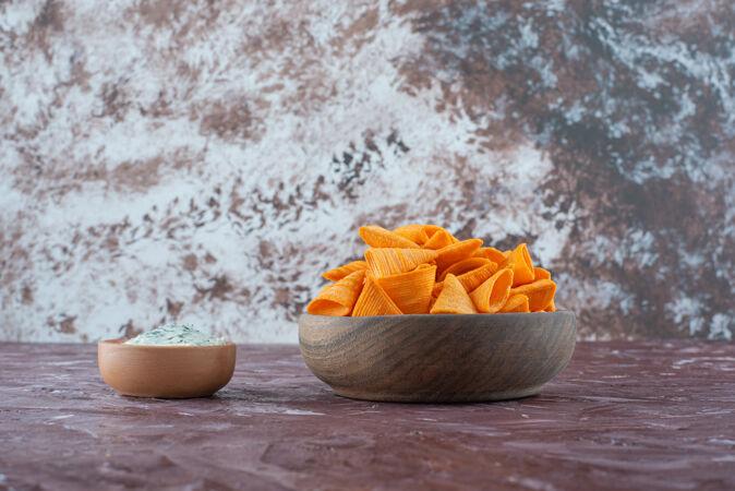 在大理石表面的碗里放上酸奶和锥形薯片