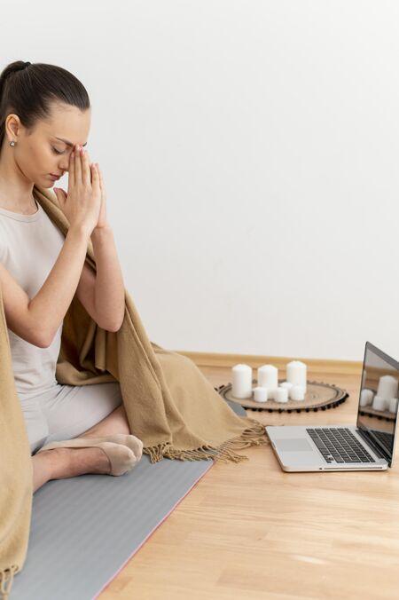 坐在家里冥想的女人 旁边放着笔记本电脑