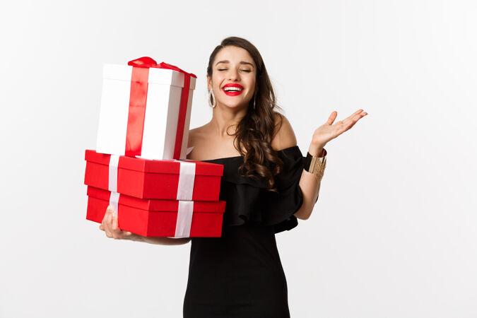 庆祝和圣诞假期的概念兴奋和快乐的女人收到礼物 拿着圣诞礼物和喜悦 站在白色背景的黑色礼服