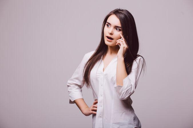 一个快乐的年轻女子在白色背景下单独打电话的全长肖像