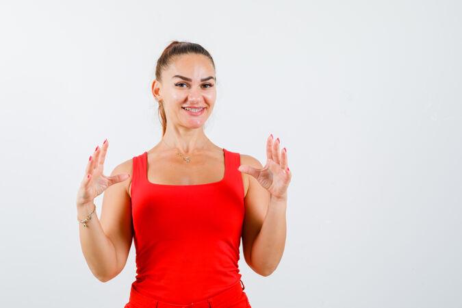 年轻女性穿着红色背心 裤子展示尺码标志 看起来很开心正面视图