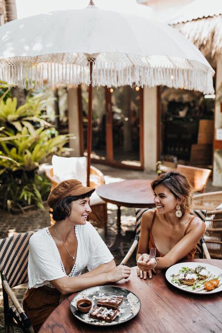 在舒适的街边咖啡馆里 穿着时髦衣服的晒黑女人微笑着说话的垂直肖像