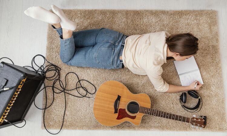 平躺的女音乐家在家里用耳机和原声吉他写歌